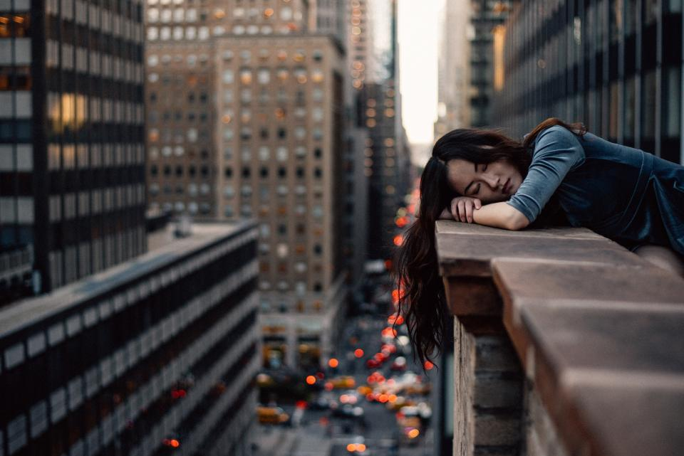 entrepreneur hanging over balcony looking over new york city