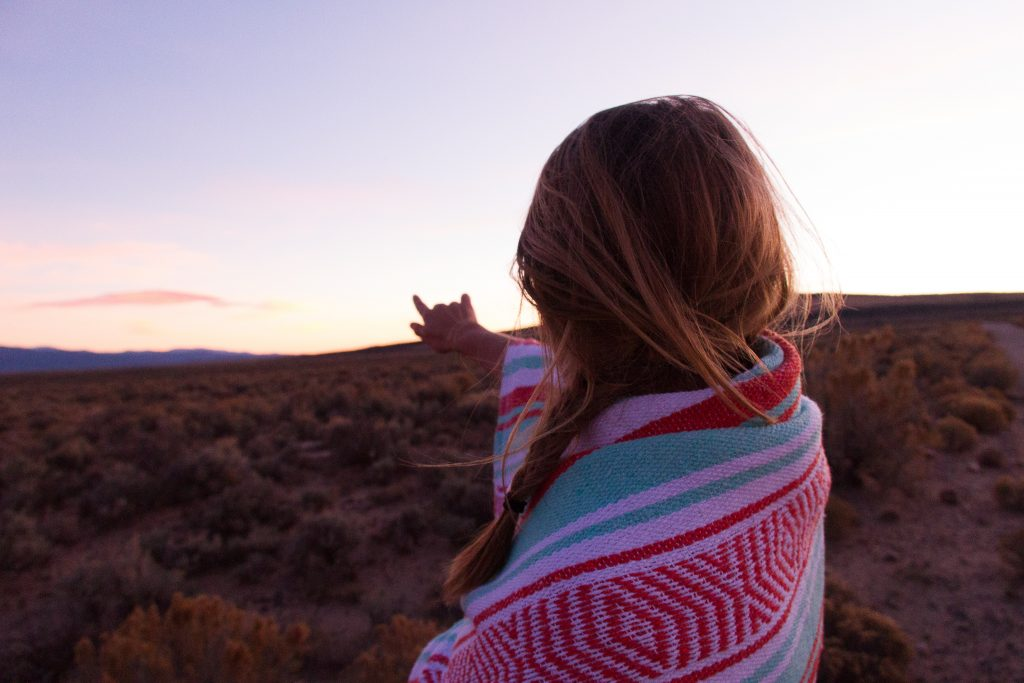 girl in desert pointing out to horizon at sunset