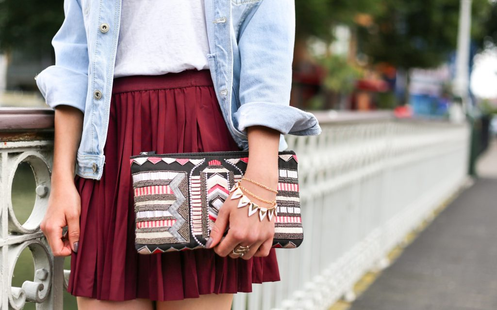 girl in red skirt holding aztec pattern clutch