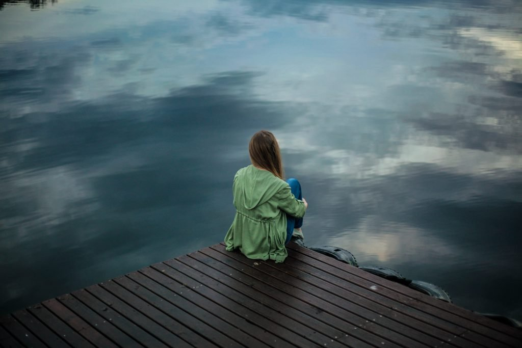 girl looking out at lake thinking about money