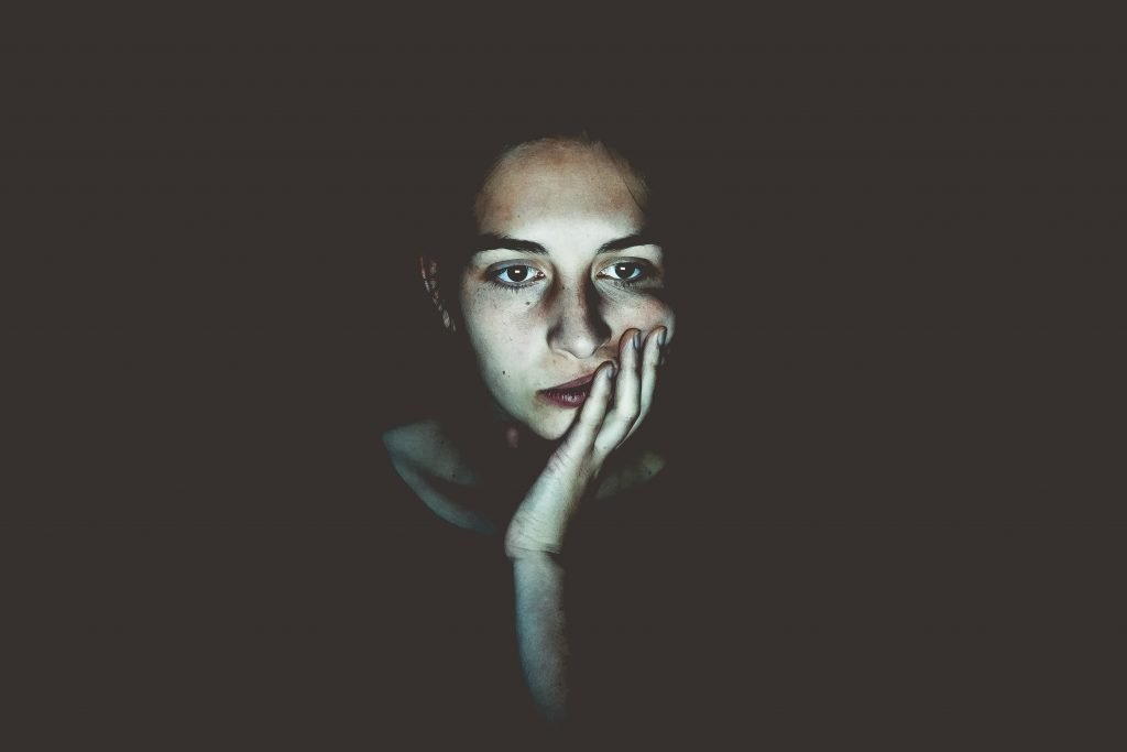 worried female entrepreneur looking at computer screen in the dark