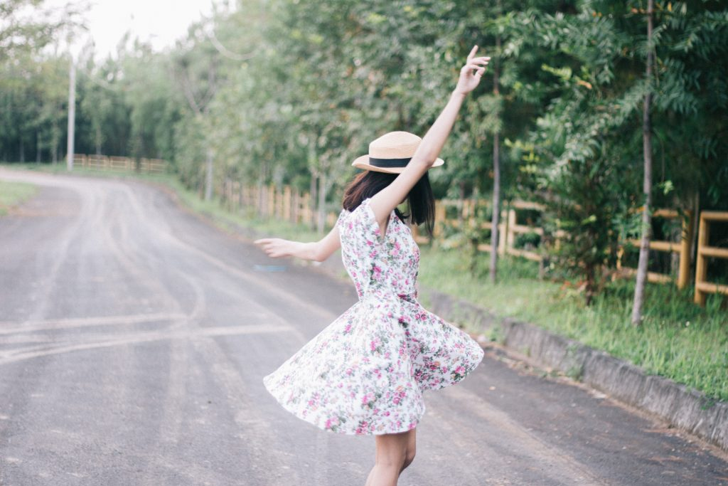 woman in floral dress and hat spinning on green country road