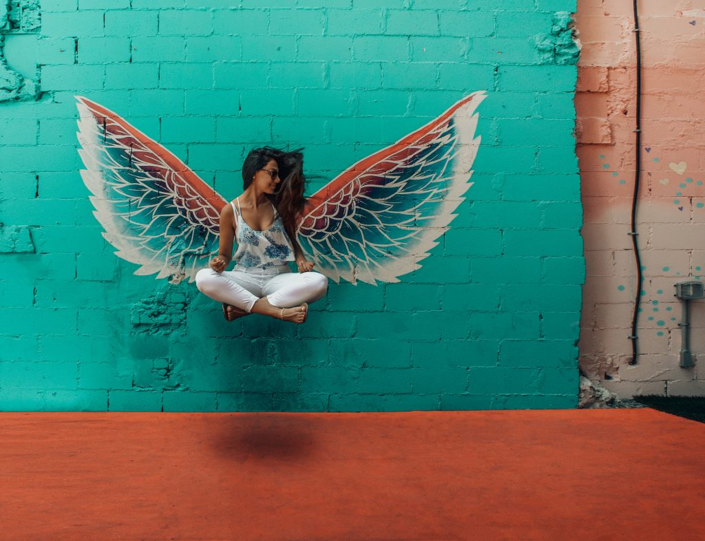 woman in front of turquoise mural with wings