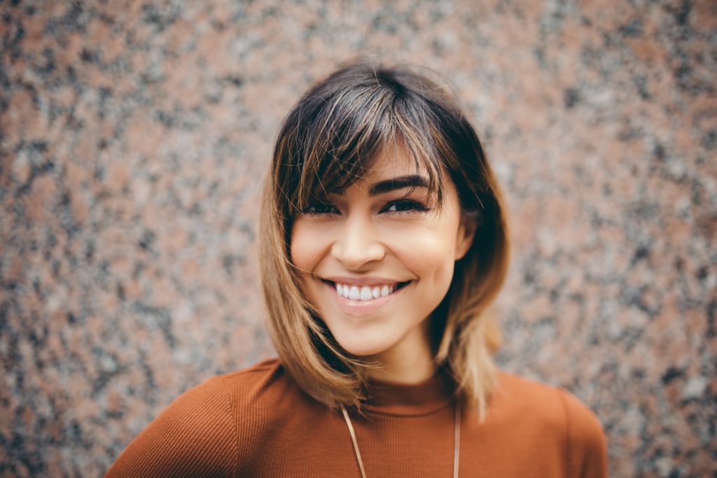 woman with short brown ombre hair smiling in front of brick wall